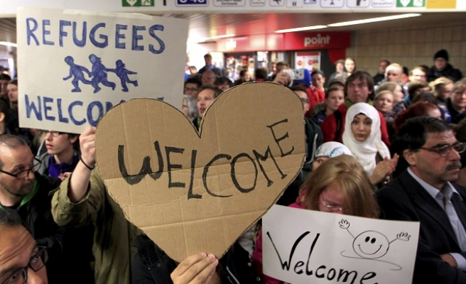 Refugees arrive in Germany to cheers, 'welcome' signs