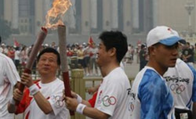 Olympics-Torch feted in Tiananmen, protesters held