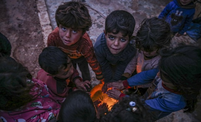 Syrian kids try to get warm around fire near their makeshift tentas rain and cold weather, which was effective tents in Kafr Lusin district where infrastructure services were insufficient, made the lives of the residents difficult during winter season in northern Idlib, Syria on January 31, 2021.