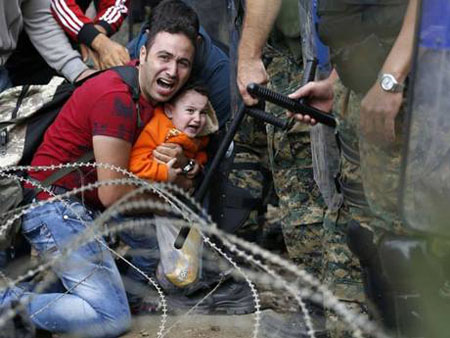 Refugees force their way over Macedonian border